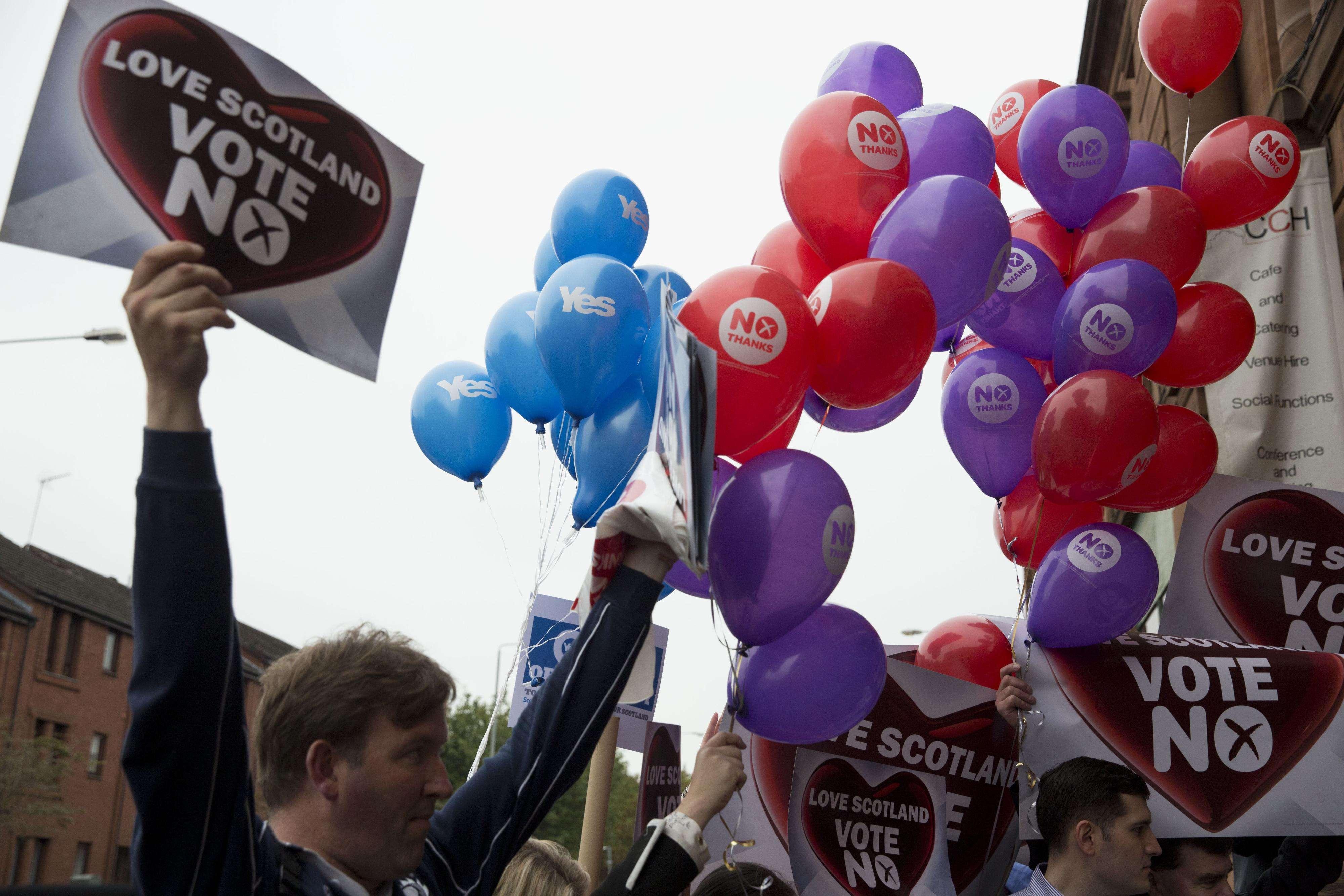 """Globos de los defensores del """"sí"""" flotan en el aire junto a los carteles de partidarios del """"no"""" en un acto electoral en Glasgow, Escocia, el 17 de septiembre de 2014. Foto: AP en español"""