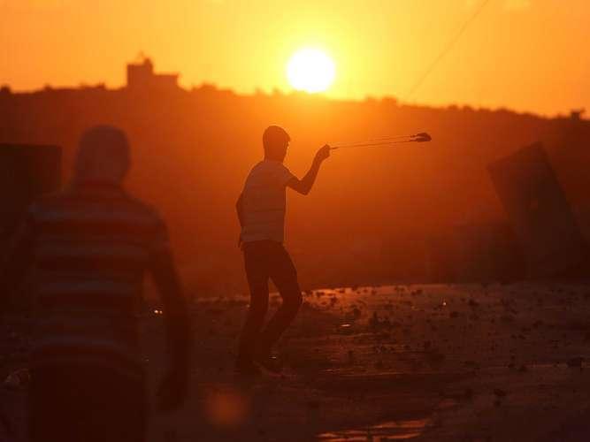 Un manifestante palestino utiliza una honda para lanzar una piedra hacia las fuerzas de seguridad israelíes durante un enfrentamiento, en Silwad, Ramala, Cisjordania. Foto: AFP en español
