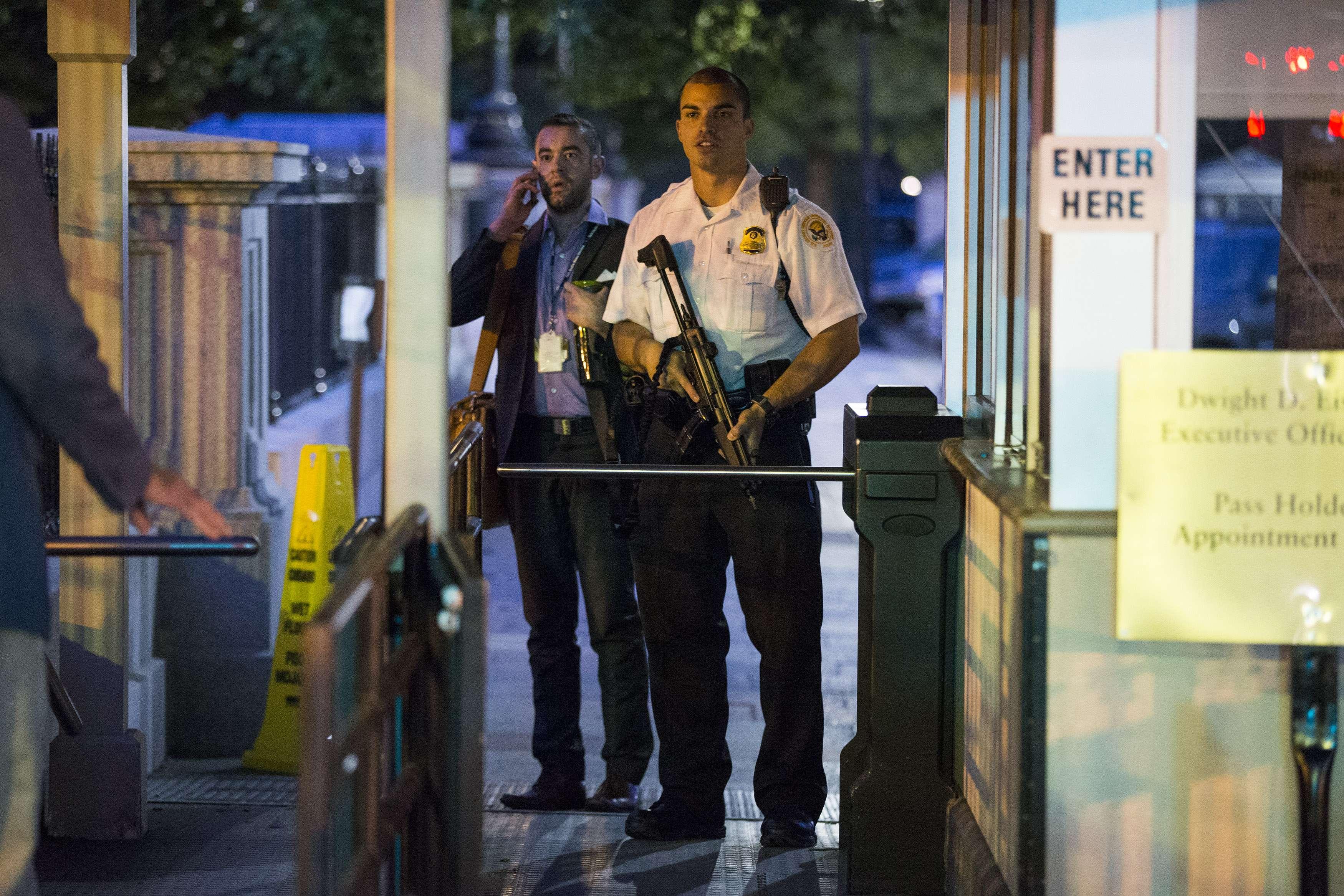 Un agente del Servicio Secreto carga su arma mientras vigila una entrada a la Casa Blanca durante un desalojo efectuado minutos después que el presidente Barack Obama partió rumbo a Camp David a bordo de un helicóptero el viernes 19 de septiembre de 2014. Foto: AP en español