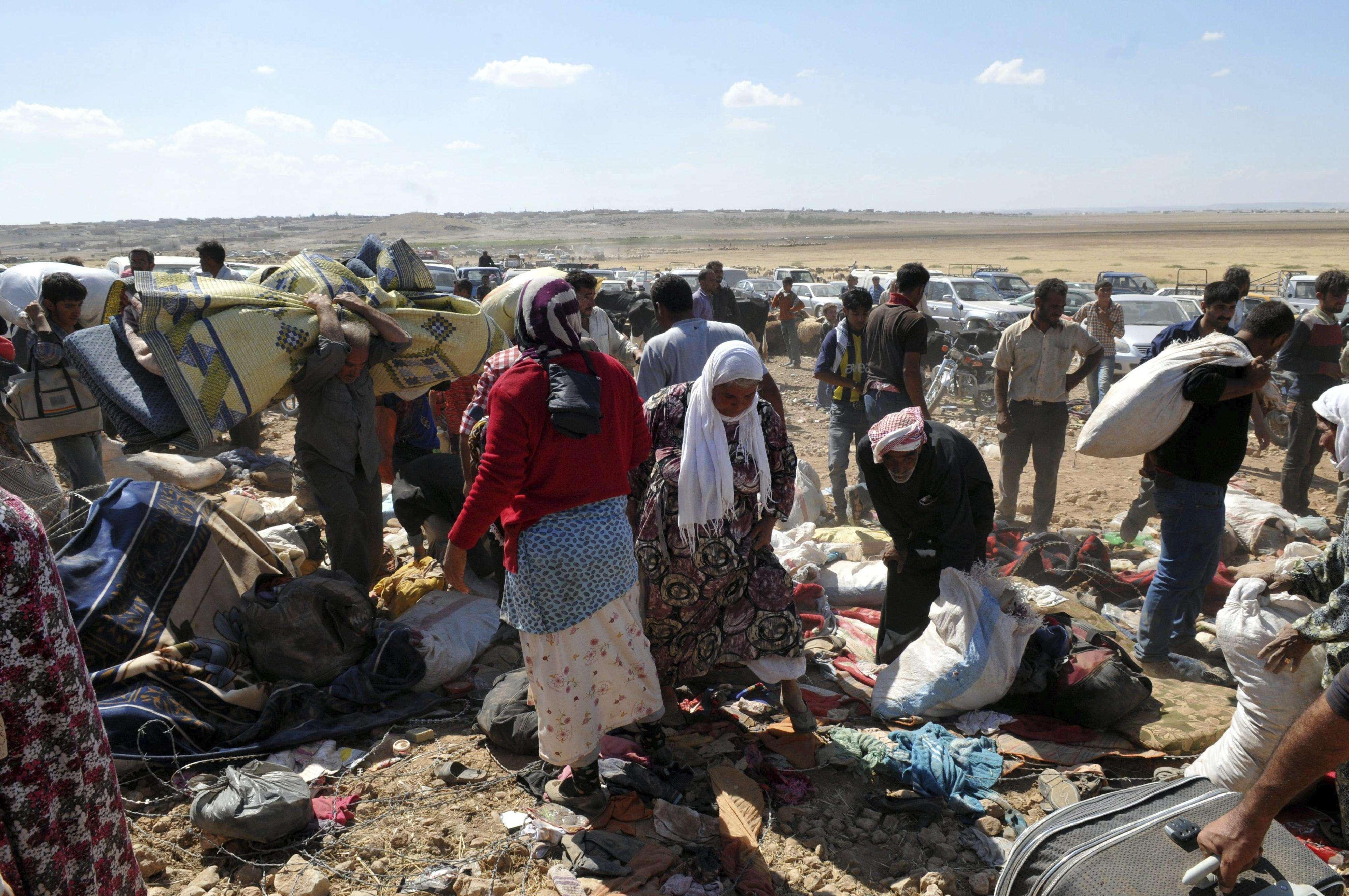 Refugiados sirios esperan en la frontera con Turquía tras dejar sus hogares, cerca de Sanliurfa, Turquía, el 19 de septiembre del 2014. Foto: EFE