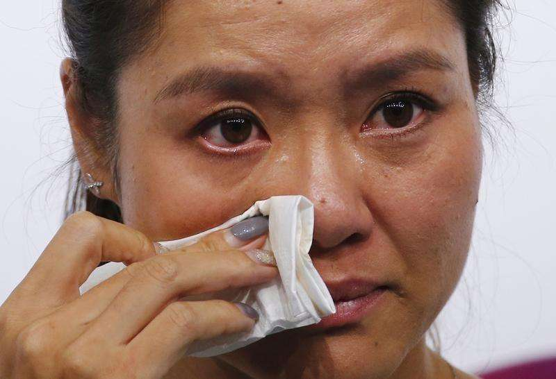 Tennis player Li Na of China wipes her tears during a news conference announcing her retirement in Beijing September 21, 2014. Foto: Petar Kujundzic/Reuters