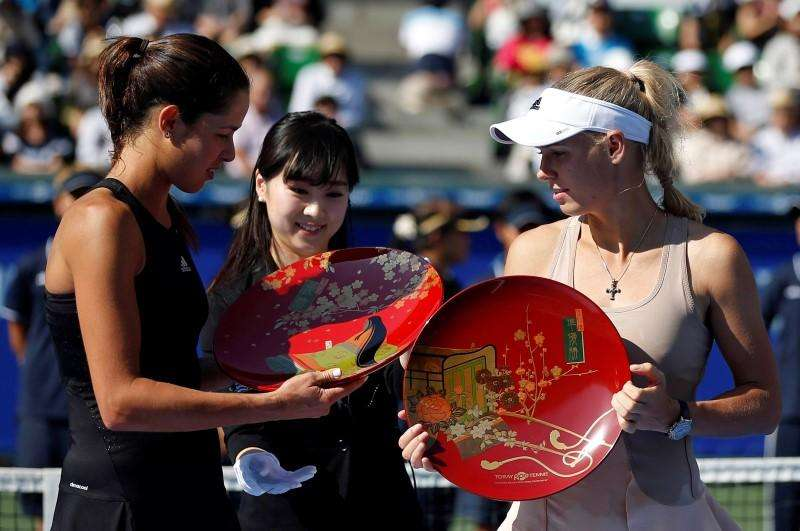 Ana Ivanovic (L) of Serbia and Caroline Wozniacki (R) of Denmark look at their trophies during an award ceremony after their Pan Pacific Open women's singles final tennis match in Tokyo September 21, 2014. Foto: Toru Hanai/Reuters