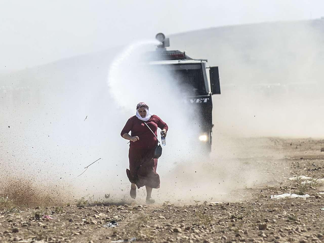 Una mujer kurda se escapa de un cañón de agua cerca de la frontera con Siria después de que las autoridades turcas cerraron temporalmente la frontera en la ciudad suroriental de Suruc en la provincia de Sanliurfa. Foto: AFP en español