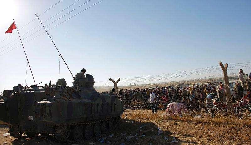 Curdos sírios aguardam na fronteira diante de soldados turcos nesta segunda-feira. Milhares deles têm fugido devido ao avanço do Estado Islâmico. Foto: Murad Sezer/Reuters
