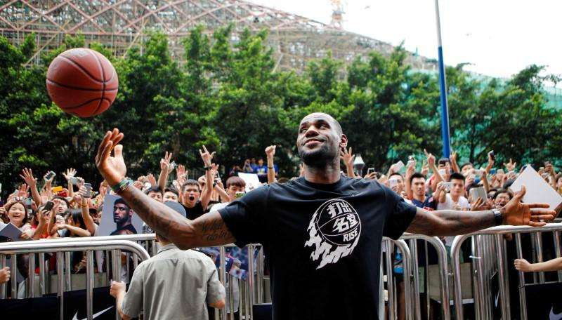 NBA basketball player LeBron James of Cleveland Cavaliers plays with a basketball during a promotional event at a store in Guangzhou, Guangdong province, July 22, 2014. Foto: Alex Lee/Reuters