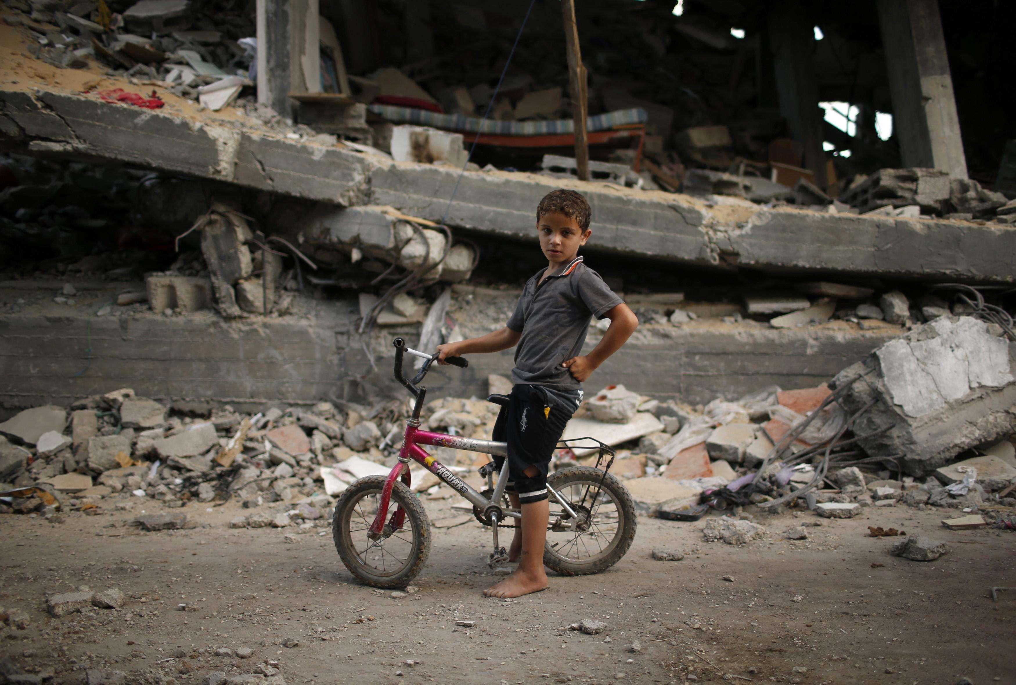 Criança palestina anda de bicicleta em meio aos escombros deixados pelo conflito na Faixa de Gaza Foto: Mohammed Salem /Reuters