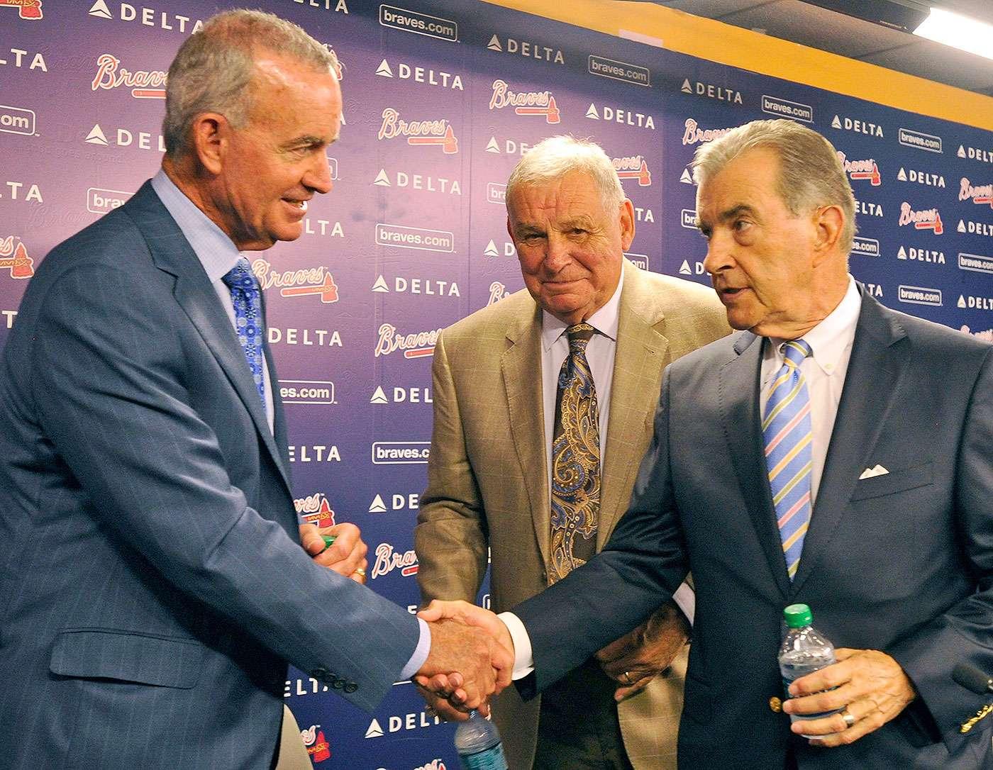 El gerente general interino de los Bravos de Atlanta, John Hart (izquierda) estrecha la mano del presidente del club, John Schuerholz, ante la mirada del ex manager, Bobby Cox. Foto: David Tulis/AP