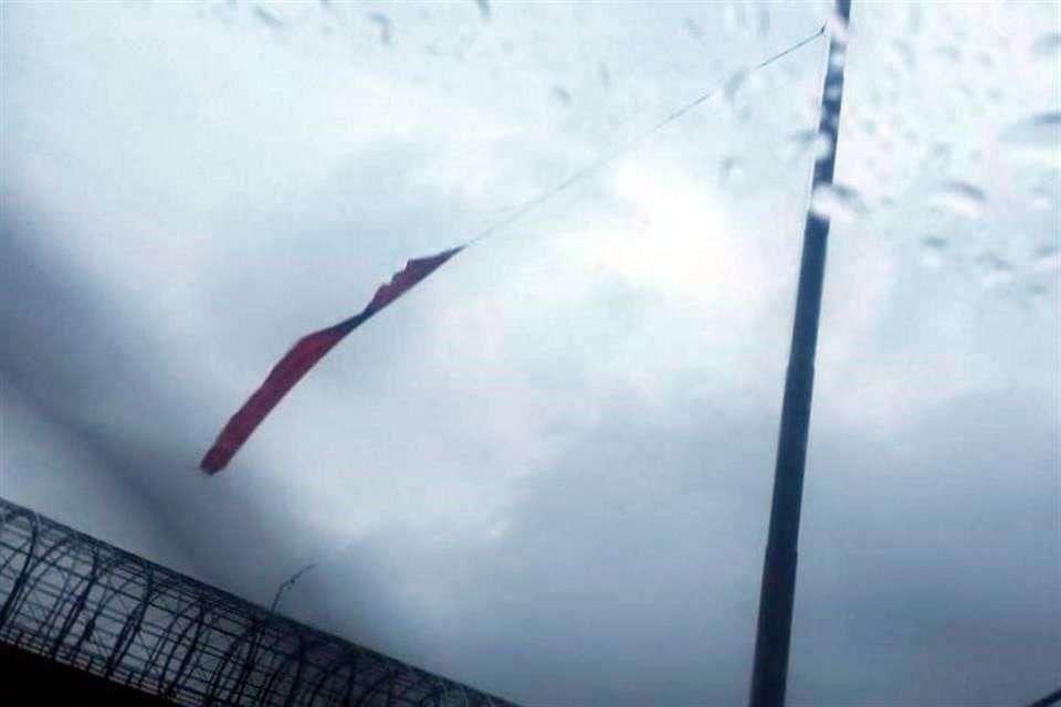 La Bandera Nacional colocada sobre Periférico Sur, a la altura de San Jerónimo, fue desgarrada por el viento y la lluvia y cayó en una fuente ubicada en la zona. Foto: Reforma/Twitter @kareme_12