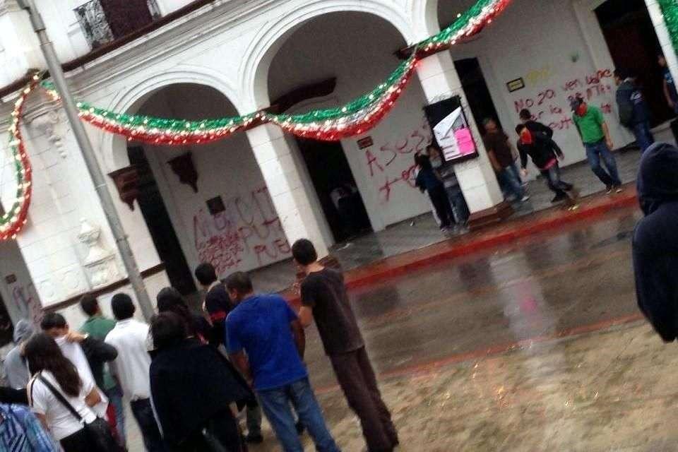 Decenas de personas atacaron con piedras y realizaron pintas contra el Palacio Municipal de Ciudad Hidalgo, Michoacán, además de prenderle fuego a un vehículo, en protesta por el asesinato de tres jóvenes presuntamente a manos de policías municipales. Foto: Reforma/Twitter