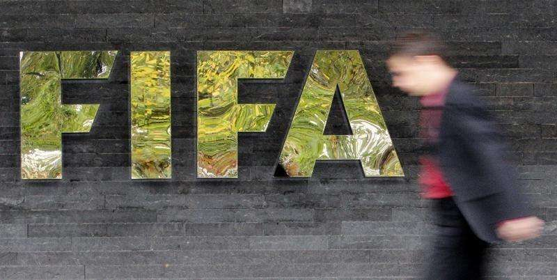 A man walks past a logo next to the main entrance of the Home of FIFA in Zurich October 20, 2010. Foto: Christian Hartmann/Reuters
