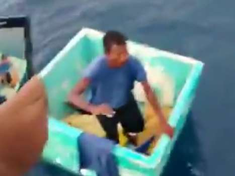 """""""¡Ya te vamos a rescatar, tranquilo!"""", le grita uno de los tripulantes de la embarcación que lo salva mientras el hombre se acerca en un cubo verde donde sobrevivió. Foto: YouTube"""