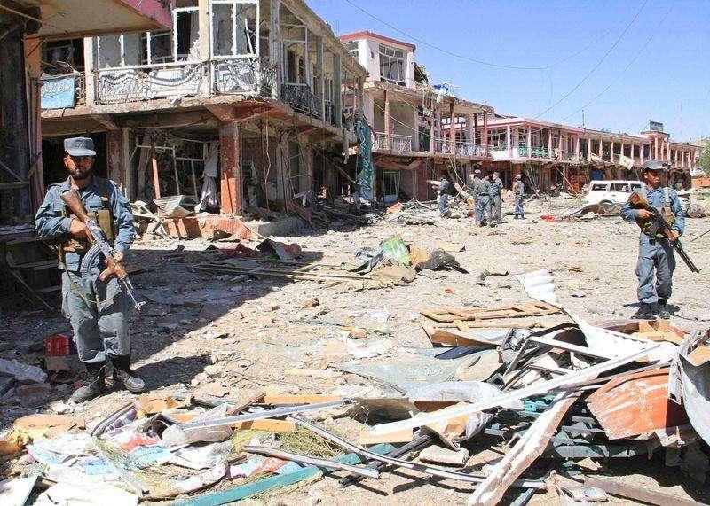 Policiais afegãos ao lado de prédios danificados após ataque suicída na província de Ghazni. 04/09/2014 Foto: Mustafa Andaleb/Reuters