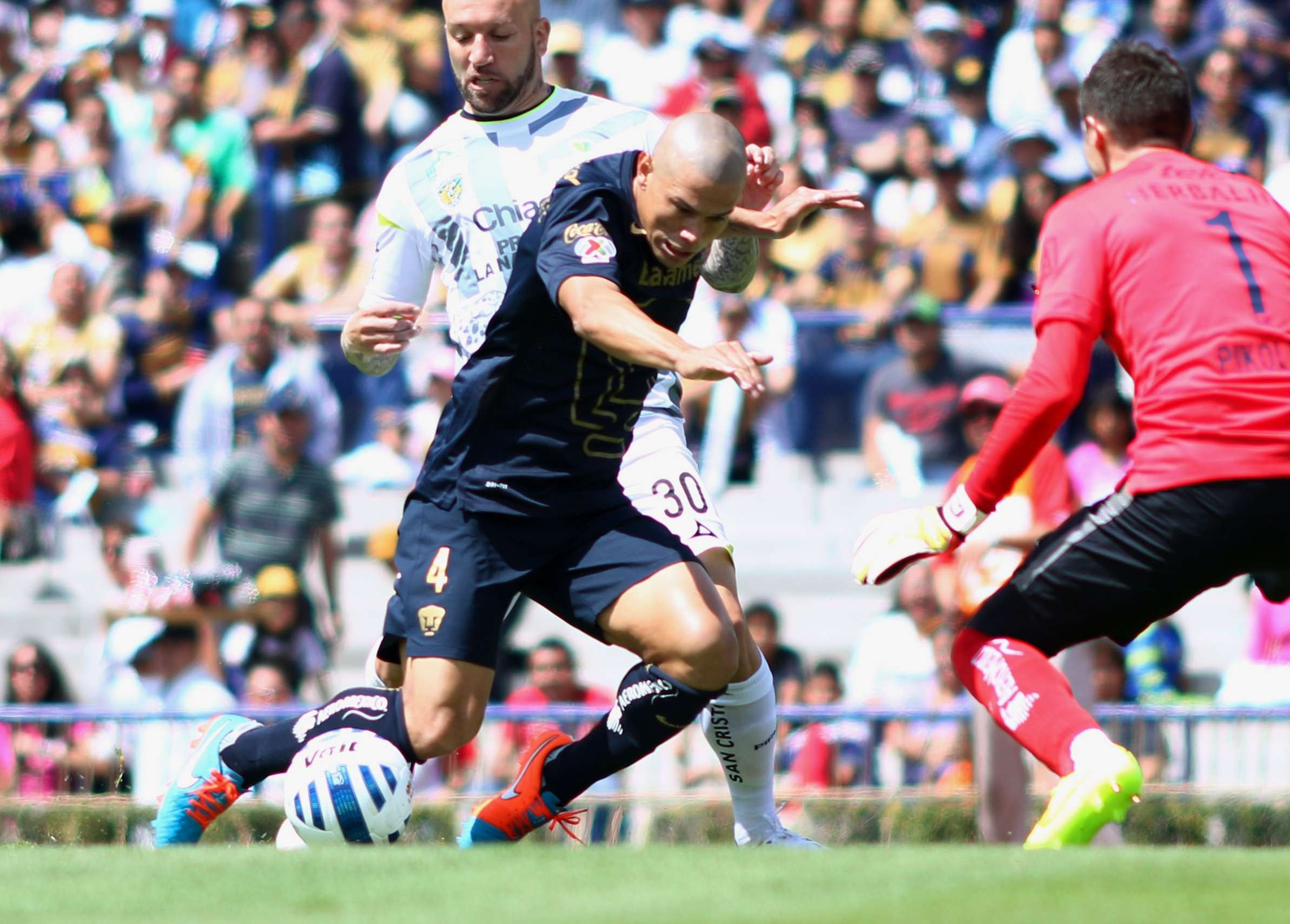 Darío Verón protege el balón de la marca de Matías Vuoso, ante la mirada de Alejandro Palacios. Foto: Imago7