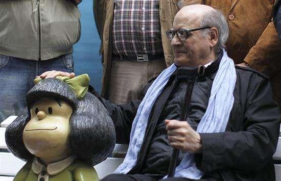 """El dibujante argentino Joaquín Salvador Lavado """"Quino"""", posa junto a una figura de su personaje Mafalda durante la presentación de dos estatuas de sus personajes. Foto: EFE en español"""
