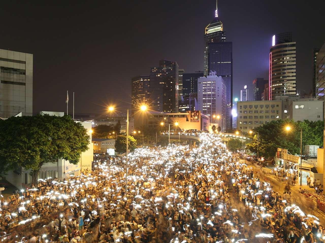 Manifestantes pro democracia sostienen sus teléfonos durante una protesta cerca de la sede del gobierno de Hong Kong. Foto: AFP en español