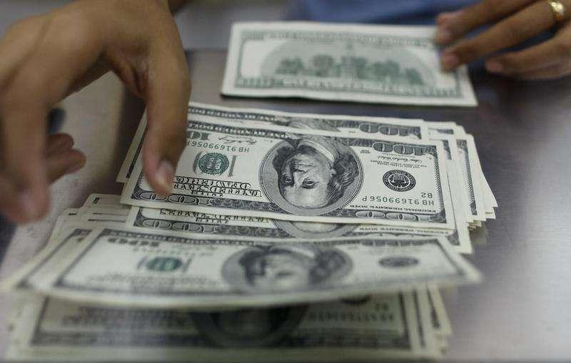 Um brasileiro troca dólares por reais em corretora de câmbio no Rio de Janeiro. 04/08/2003 Foto: Bruno Domingos REUTERS/Reuters