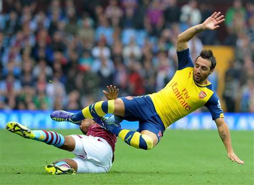 Arsenal's Santi Cazorla, right, is tackled by Villa's Fabian Delph during the English Premier League soccer match between Aston Villa and Arsenal at Villa Park, Birmingham, England, Saturday, Sept. 20, 2014. Foto: Rui Vieira/AP en español