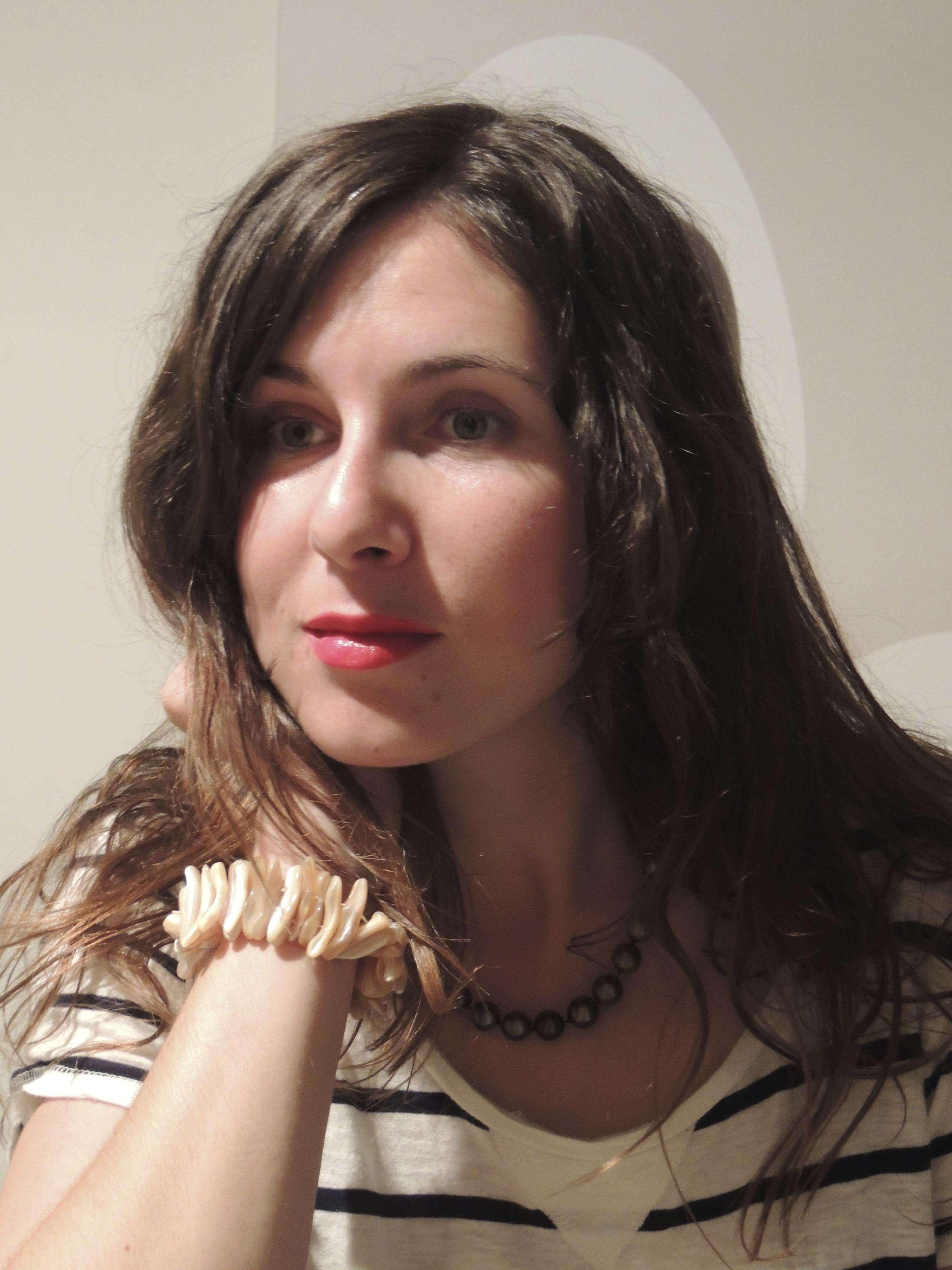 Una mujer joven, con pigmentos ocres rojos en los labios y joyas hechas con perlas Foto: Carlos Duarte
