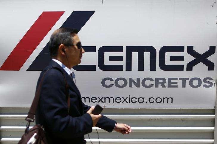 Una persona pasa frente al logo de la empresa mexicana Cemex en Ciudad de México. Imagen de archivo, 27 agosto, 2014. La mexicana Cemex, una de las mayores cementeras del mundo, dijo el martes que obtuvo un nuevo crédito bancario por 1,350 millones de dólares, que mejora las condiciones establecidas en su actual acuerdo financiero y que utilizará para refinanciar deuda. Foto: Edgard Garrido/Reuters