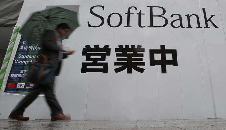 A man holding an umbrella walks past the logo of Softbank Corp at its branch in Tokyo April 22, 2014. Foto: Yuya Shino/Reuters
