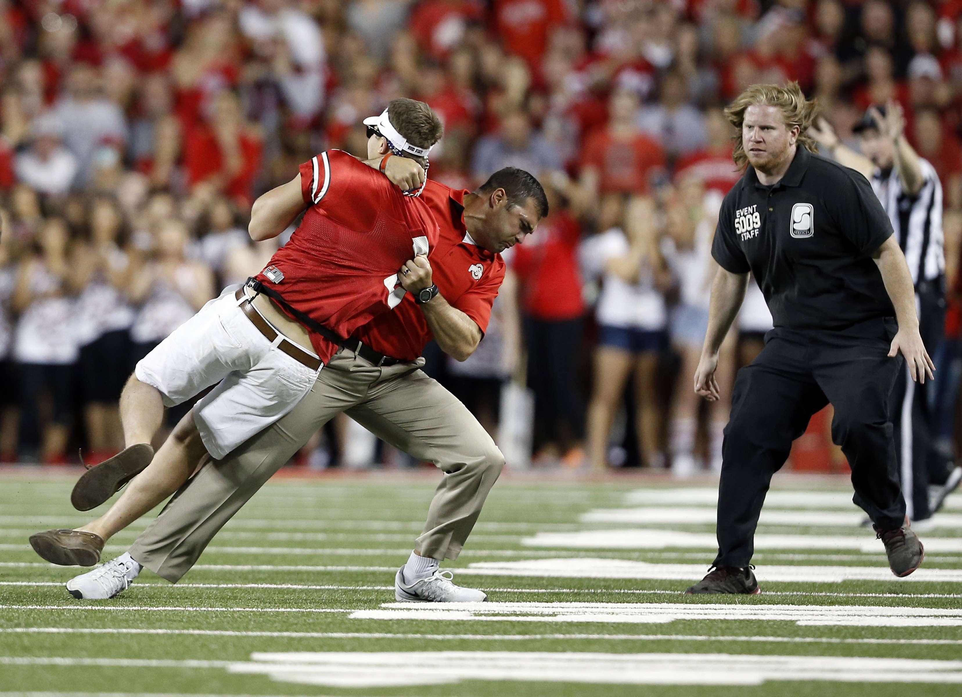 Treinador-assistente de força da universidade de Ohio State deu um tackle em invasor de campo Foto: Adam Cairns/AP