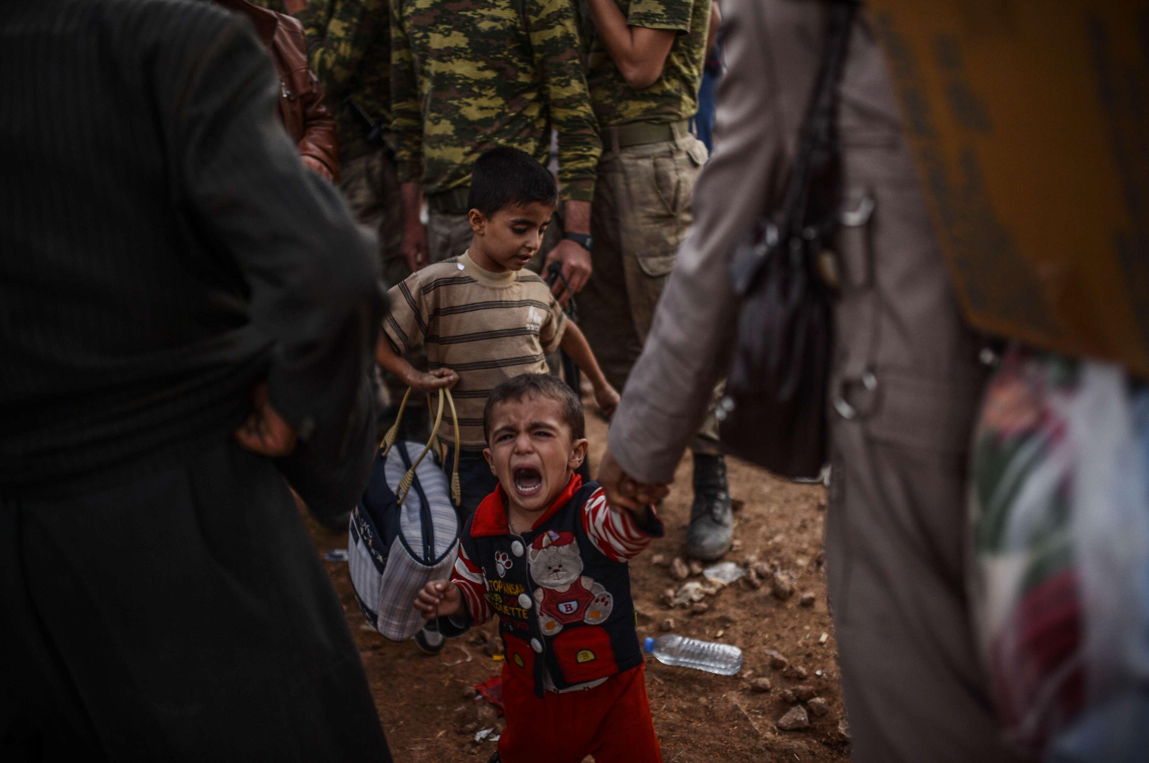 Criança curda chora ao chegar na Turquia após fugir com família de confrontos no território sírio Foto: BULENT KILIC/AFP