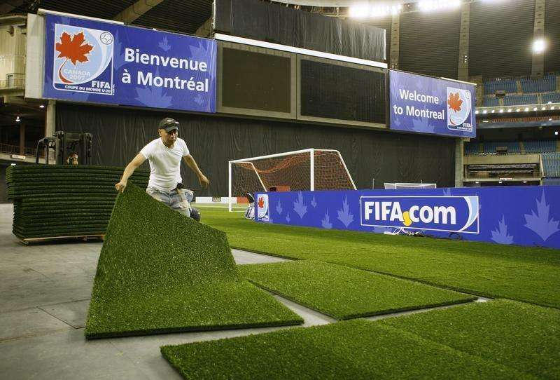 A worker puts down turf at Olympic Stadium in Montreal in preparation for the FIFA U-20 World Cup soccer tournament, June 28, 2007. Foto: Shaun Best/Reuters