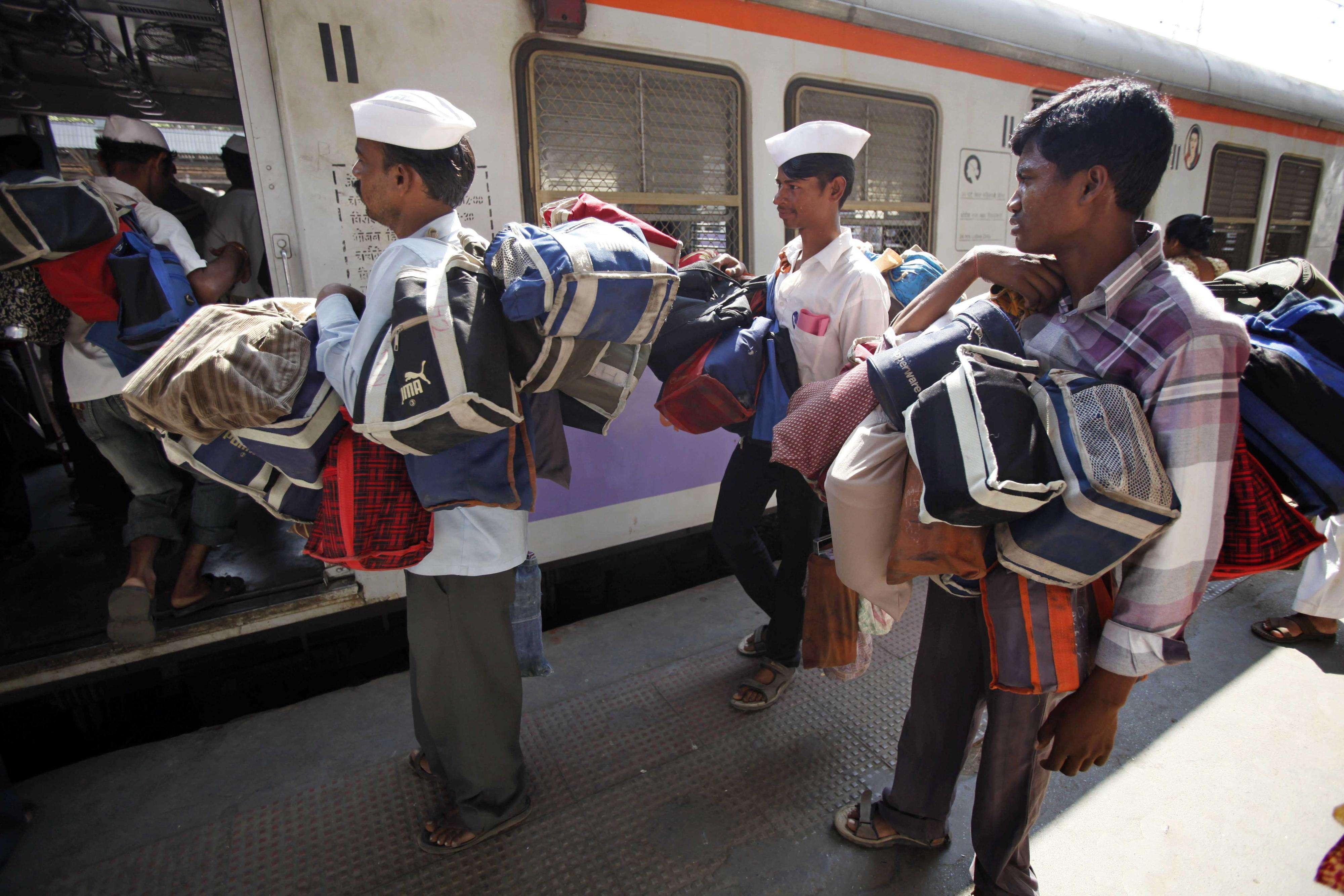 Llueva, truene o relampaguee, los dabbawalas de India llevan y traen los envases de comida casera a sus destinatarios. Foto: AP en español