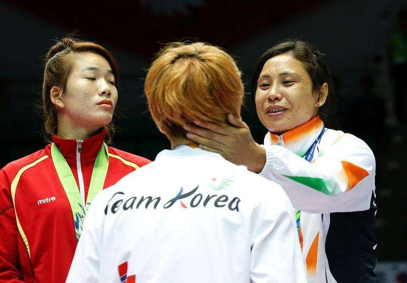 India's bronze medallist Laishram Sarita Devi (R) talks with South Korea's silver medallist Park Ji-na during the medal ceremony for the women's light (57-60kg) boxing competition at the Seonhak Gymnasium during the 2014 Asian Games in Incheon October 1, 2014. Foto: Kim Kyung-Hoon/Reuters