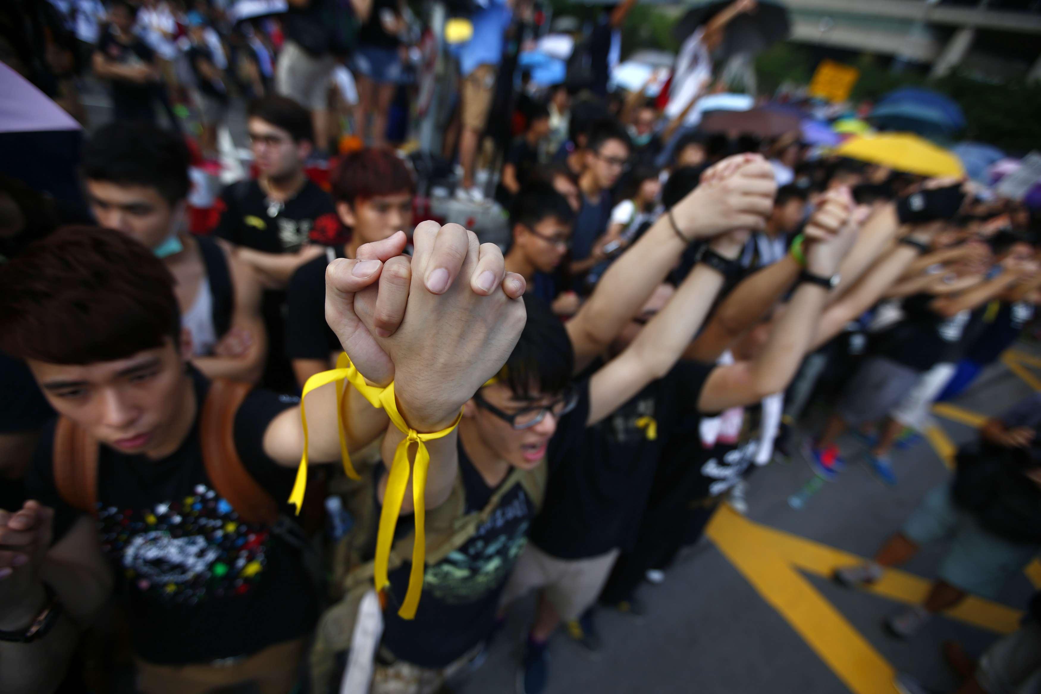 O clima era calmo entre a multidão de manifestantes, apesar de alguns apelos para tentar forçar o cordão de isolamento policial perto da praça Golden Bauhinia Foto: Carlos Barria /Reuters