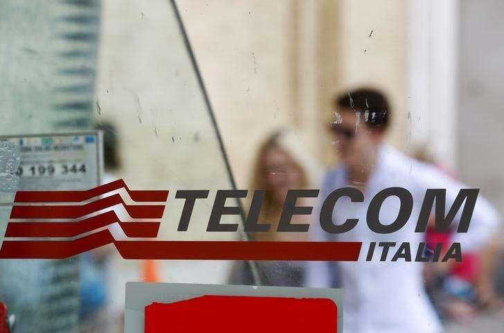 Pessoas passam atrás de um logotipo da Telecom Italia em Roma. Foto: Max Rossi/Reuters
