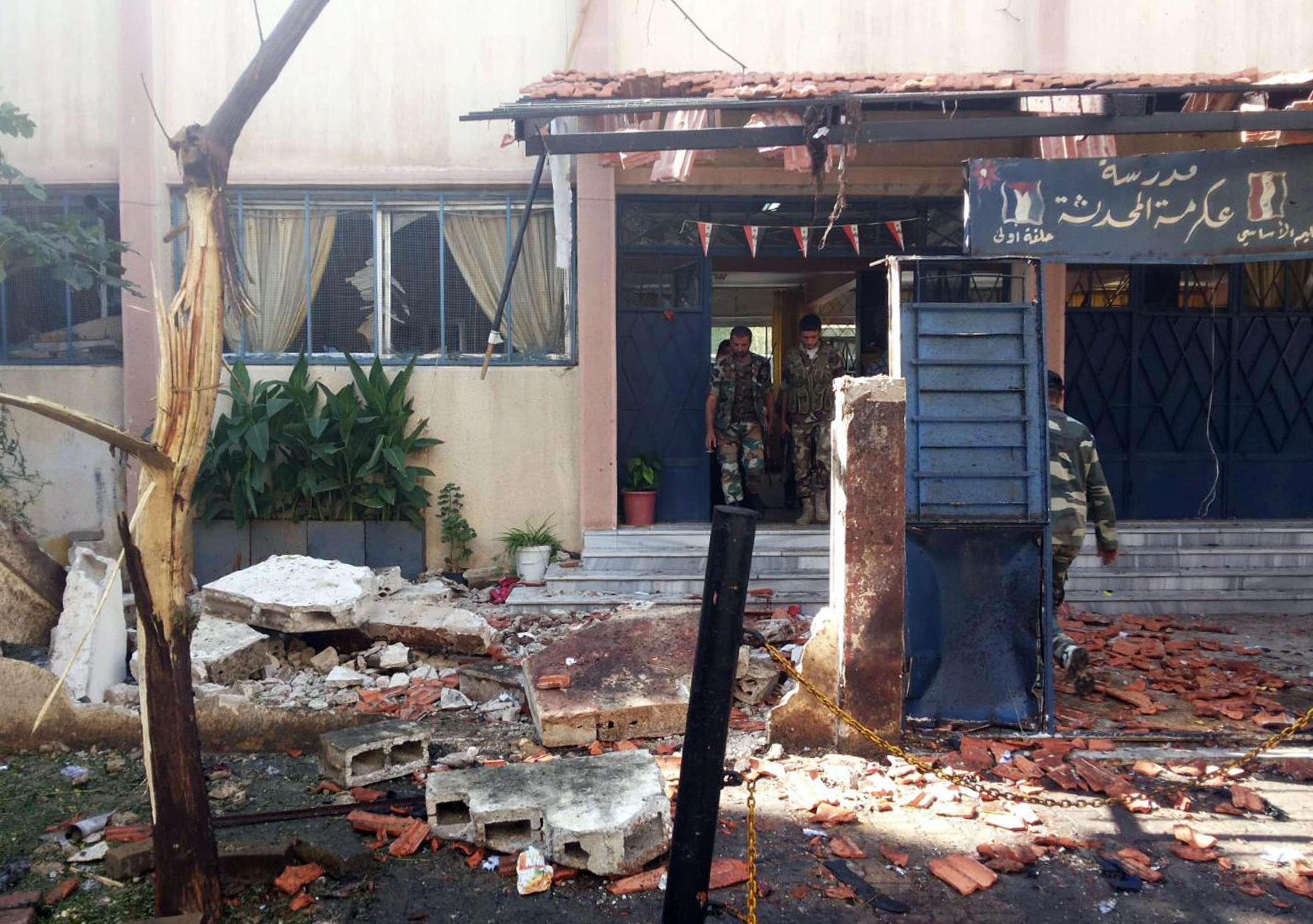 Polícia faz inspeção próximo de área onde dois carros-bombas explodiram nesta quarta-feira Foto: SANA/AFP