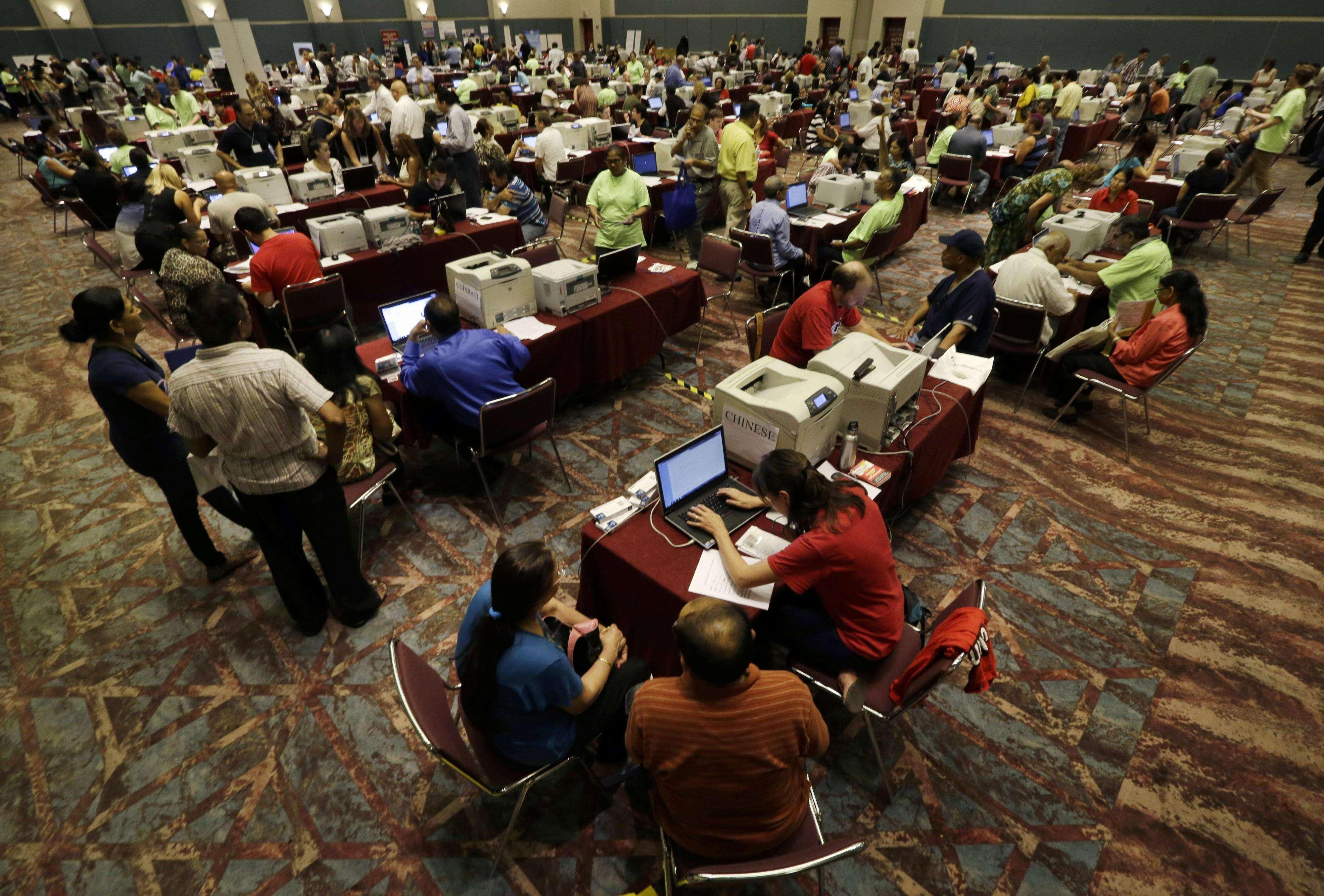 En esta imagen de archivo del 3 de septiembre de 2014, varias personas llenan solicitudes para subsidio gubernamental por desempleo en una sala del Centro de Convenciones de Atlantic City, Nueva Jersey. Foto: AP en español