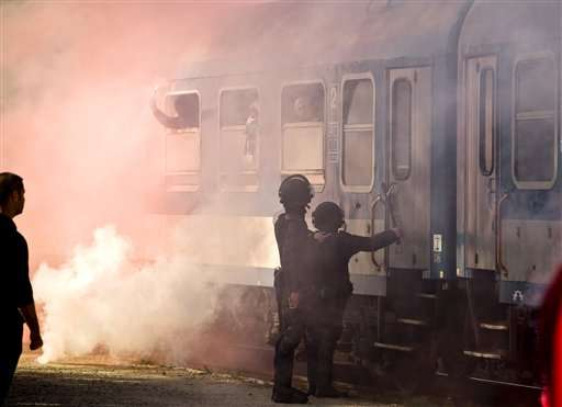 Romanian riot policer officers check the door of a train, engulfed in smoke from flares, transporting Hungarian soccer fans at a railway station in Bucharest, Romania, Saturday, Oct. 11, 2014. Romanian authorities took exceptional security measures to prevent violence between soccer fans ahead of a Euro 2016 Group F qualifier soccer match between Romania and Hungary. Foto: AP en español