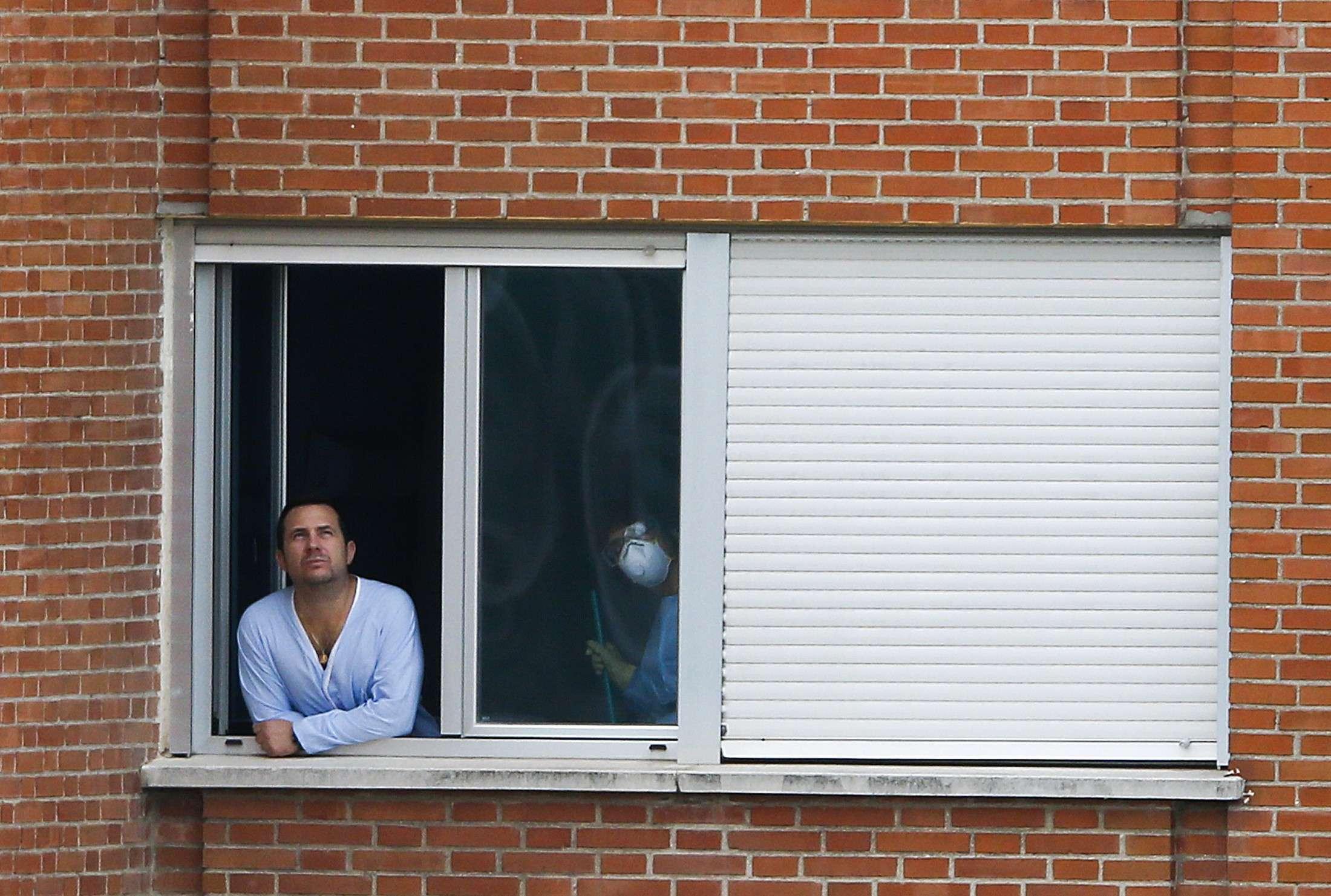 Marido da enfermeira espanhola com ebola aparece em janela do Hospital Carlos III, em Madri Foto: Paul Hanna/Reuters