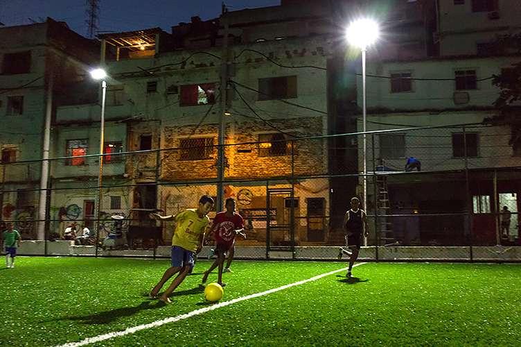 Jovens jogam em campo de futebol com energia elétrica criada por meio de placas que captam cinética no Morro da Mineira Foto: Shell/Divulgação