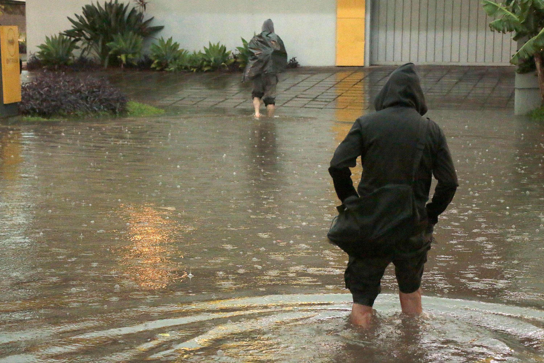 Homem tenta atravessar a rua alagada em Porto Alegre em dia de temporal Foto: Fernando Teixeira/Futura Press