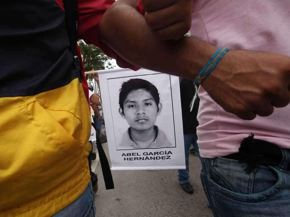 Unidos de los brazos, avanzaron familiares de los normalistas de Ayotzinapa portando imágenes de los jóvenes. Foto: Terra