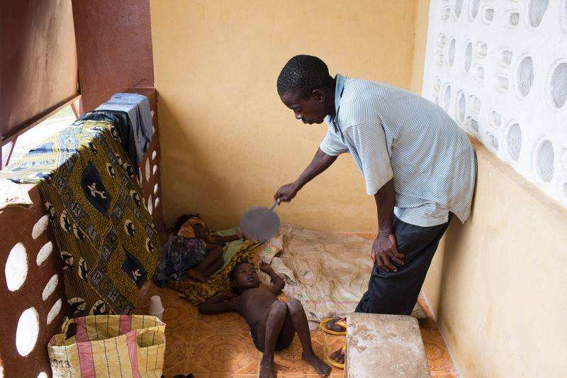 Ibrahim Sorie Kamara cuida de seus filhos à espera de transporte para um centro de tratamento contra o Ebola, em Foredugu, Serra Leoa, no início de outubro. 08/10/2014 Foto: Christopher Black/Reuters
