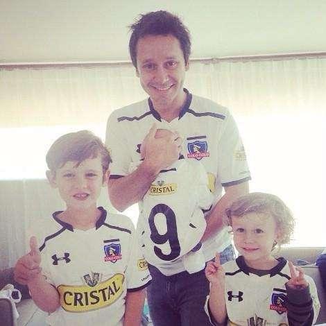 Benjamín tiene en brazos a Benicio y posa junto a Bautista y Beltrán, sus otros hijos, vestidos con camisetas de Colo Colo Foto: Facebook