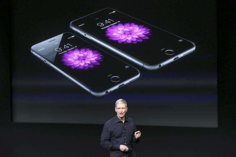 El fabricante de dispositivos tecnológicos Apple Inc comunicó un alza de sus ingresos de un 12 por ciento, mayor a la esperada, porque el lanzamiento de su nuevo iPhone ayudó a impulsar ventas de 39,27 millones de teléfonos avanzados en el trimestre terminado en septiembre. En la imagen, el consejero delegado de Apple, Tim Cook, de pie ante una pantalla con el iPhone 6 durante una presentación en la sede californiana de Cupertino el 16 de octubre de 2014. Foto: Robert Galbraith/Reuters