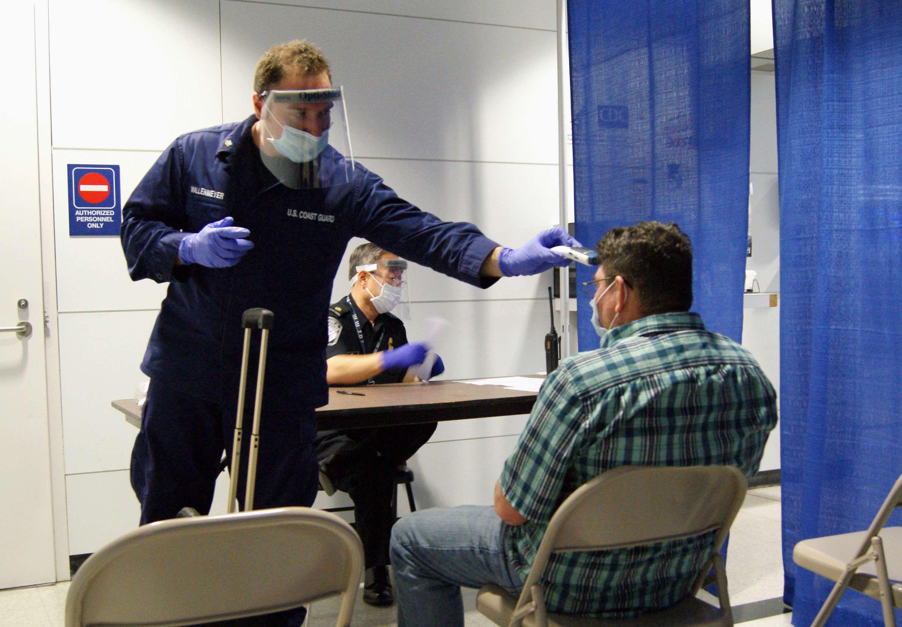 Personal del Servicio de Inmigración y Control de Aduanas llevan a cabo pruebas en un pasajero que llegó de Sierra Leona al aeropuerto O'Hare de Chicago. Foto: AP en español