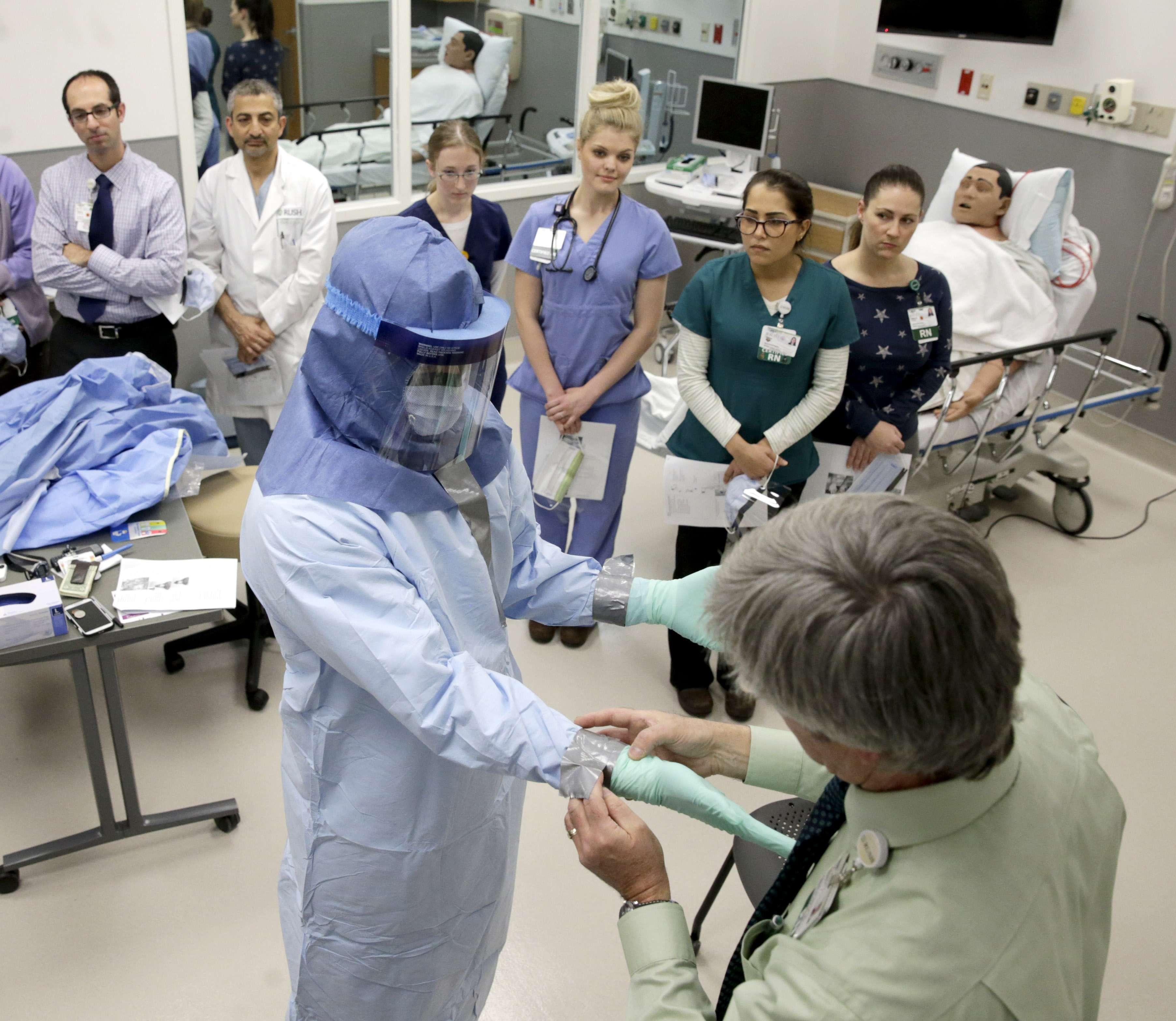 La enfermera Keene Roadman totalmente vestida con uniforme especial y el enfermero Fred Serafin, a la derecha, muestran los procedimientos para el uso del equipo protector en la atención de pacientes con ébola en el Centro Médico de la Universidad Rush en Chicago, Foto: AP en español