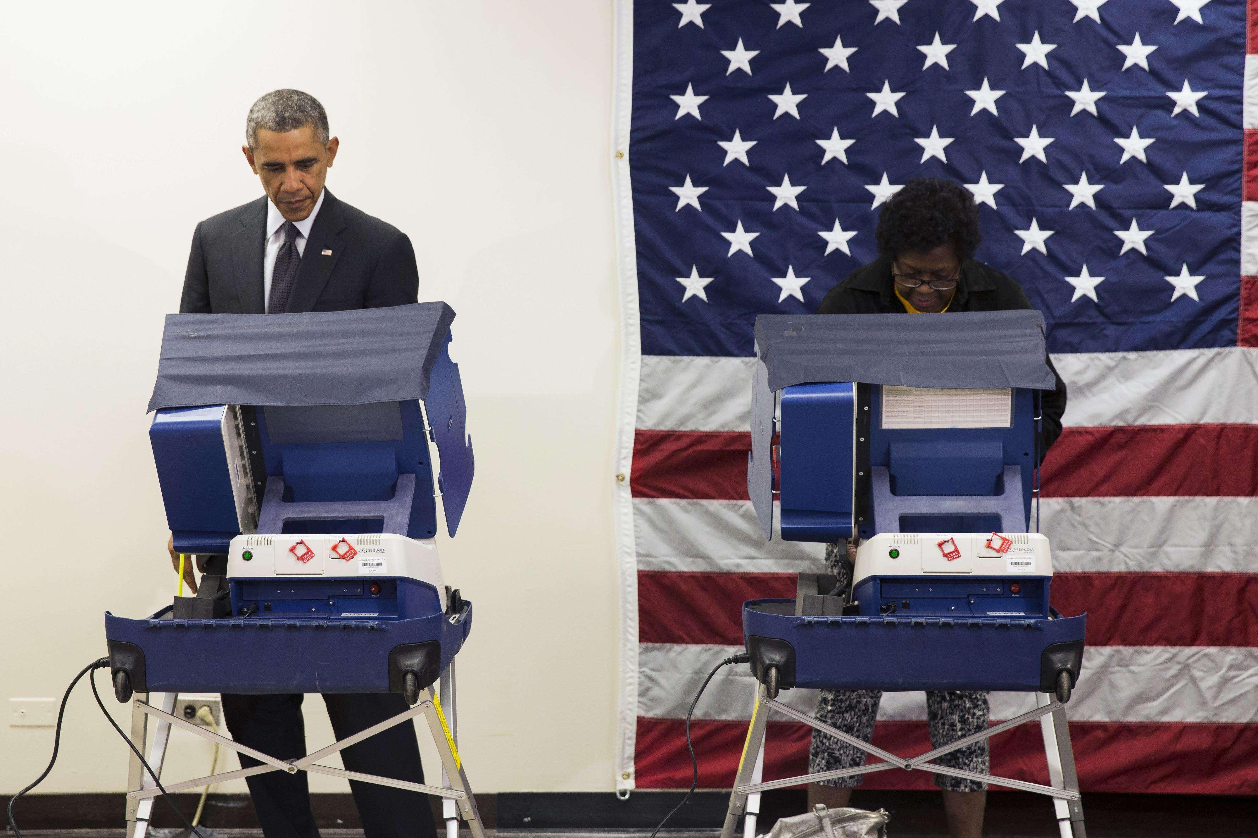 Barack Obama, izquierda, vota anticipadamente en las elecciones al Congreso de 2014 en el Centro Comunitario Dr. Martin Luther King, lunes 20 de octubre de 2014. Foto: AP en español