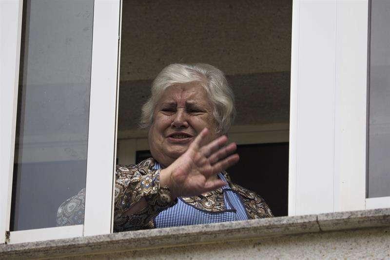 Jesusa Ramos, madre de la auxiliar de enfermería Teresa Romero, saluda a los periodistas en la ventana de su casa de Becerreá (Lugo) tras conocer la noticia de que su hija ha superado la infección del virus del Ébola. Foto: Eliseo Trigo/EFE en español