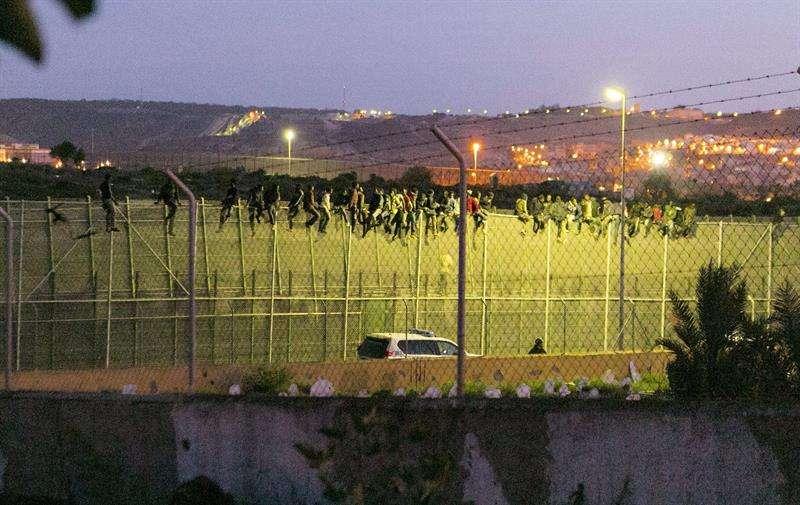 Los inmigrantes subidos a la valla. Foto: EFE en español