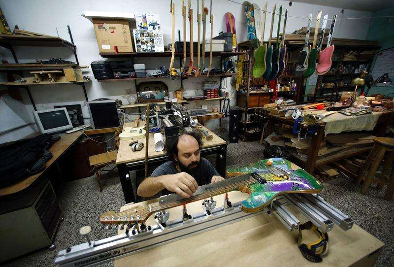Argentine luthier Ezequiel Galasso works on a guitar he made out of skateboards at his workshop in Buenos Aires October 17, 2014. Foto: Marcos Brindicci/Reuters
