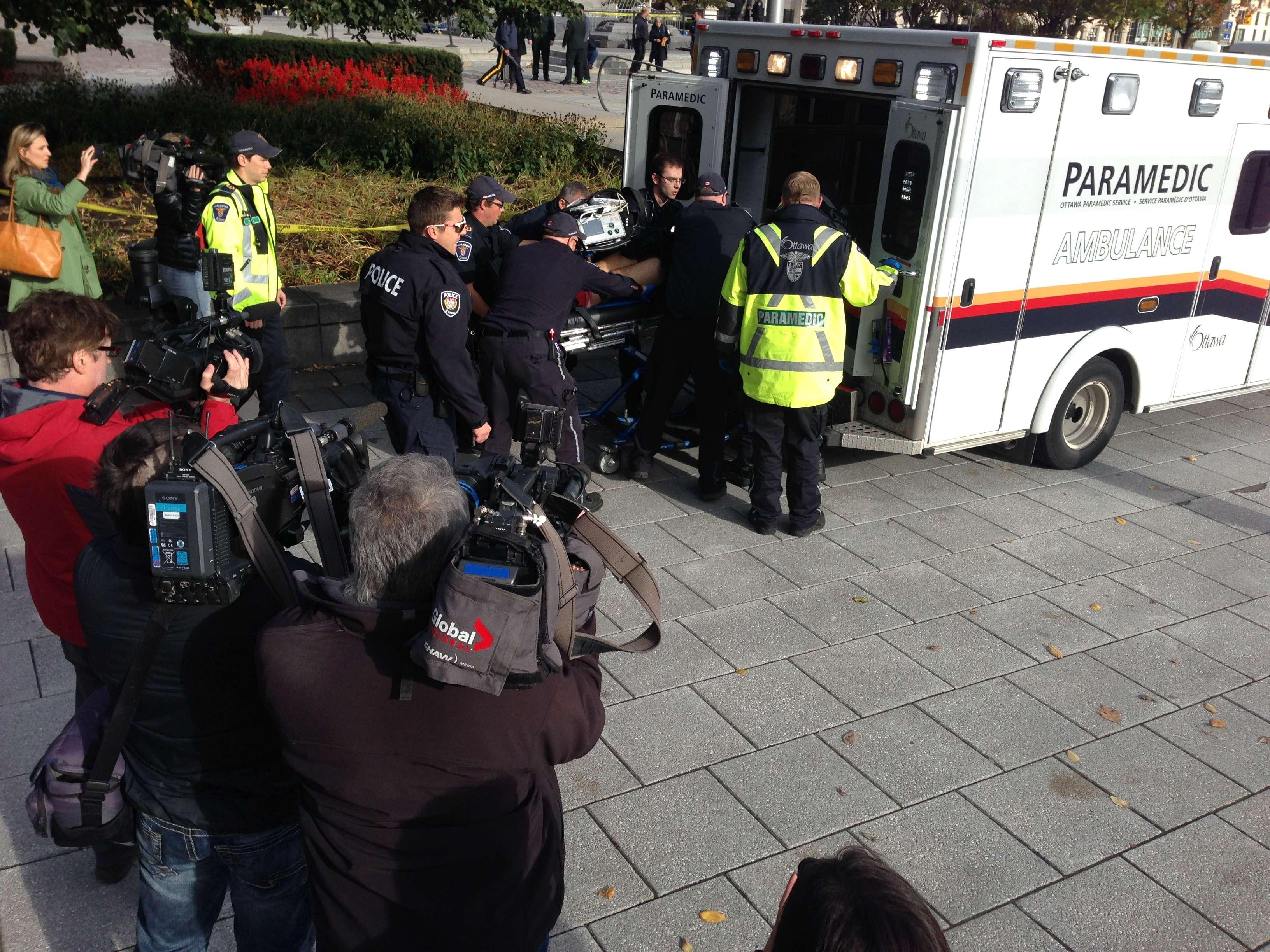 Soldado ferido a tiros perto do Parlamento do Canadá é movido para dentro de uma ambulância por policiais e médicos Foto: Michel Comte/AFP