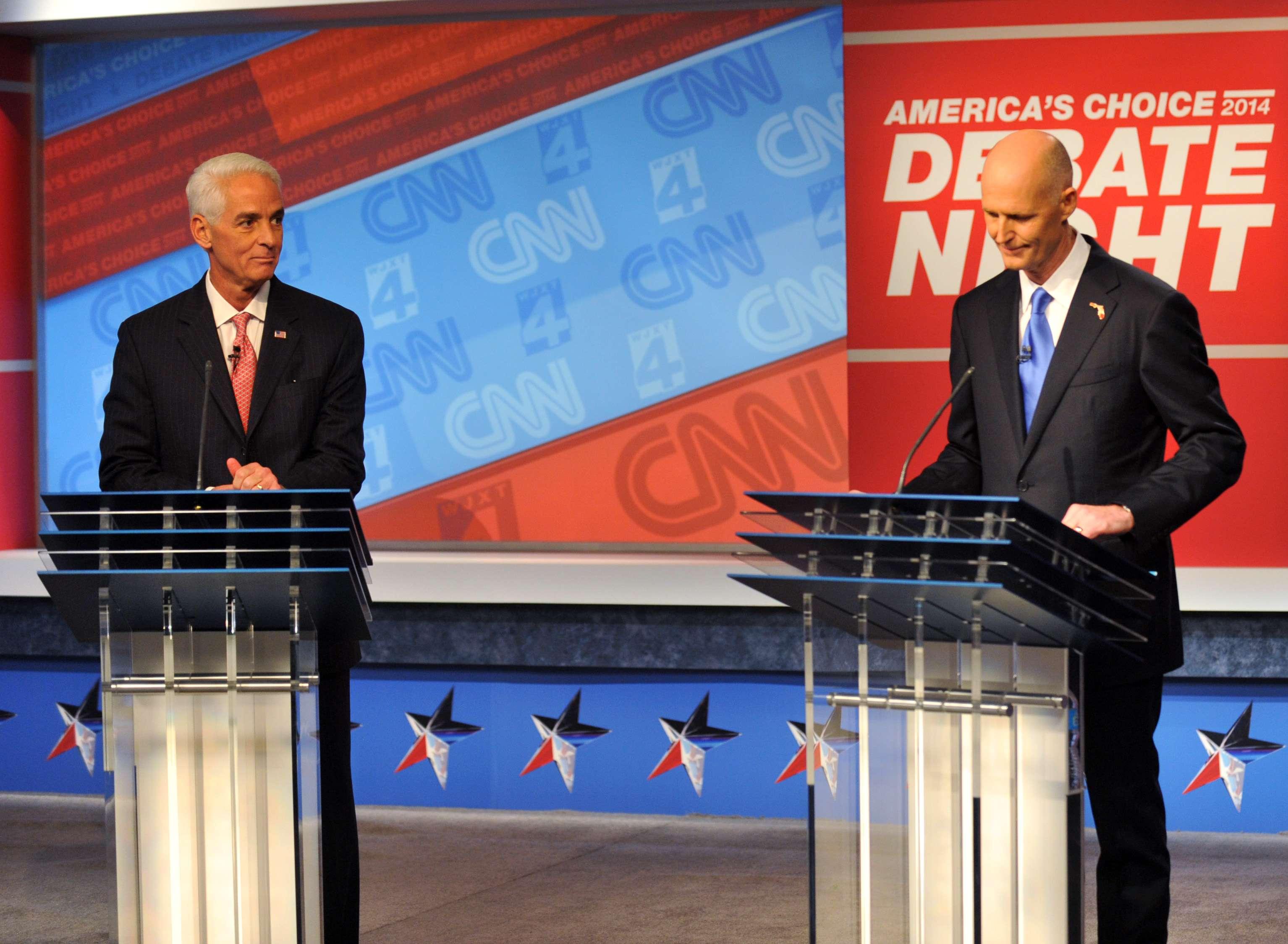 El candidato demócrata Charlie Crist, izquierda, y el gobernador republicano Rick Scott esperan el inicio de su debate televisado, el martes 21 de octubre de 2014, en los estudios de Channel 4 en Jacksonville, Florida. Foto: AP en español
