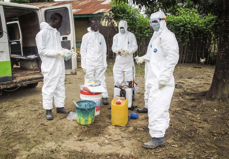 Trabajadores sanitarios visten trajes de protección antes de entrar en la vivienda de una persona que supuestamente falleció por ébola en la comunidad de Port Loko, a las afueras de Freetown, Sierra Leona, el 21 de octubre de 2014. Foto: AP en español